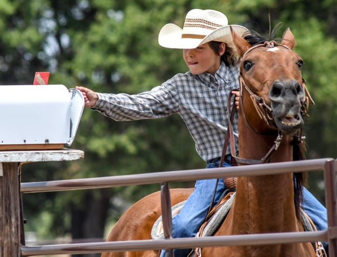 Cort Baker opens a mailbox from horseback to grab a rock inside and show the judges Saturday while competing in the intermediate Trail category of the Finney County Fair's Horse Show at the fairgrounds. The show provided a look at participants showmanship and abilities with their horses.  The fair is in full swing this week, with events running through Sunday at the fairgrounds.