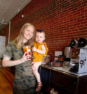 """Kristin Priest and her 15-month-old daughter AnnaLynne are shown in Priest's new business, """"Grace and Grit Nutrition,"""" located in downtown Geneseo."""