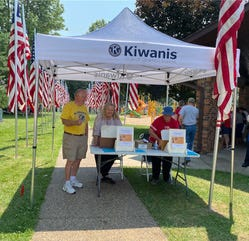 """Kiwanis Club members, including Bob Mays, Claire Crawford and Jeanne Anderson are shown working at the recent Kiwanis Club's annual July 4th """"Pork in the Park"""" event, making good use of one of the two tents purchased recently by the Club with memorial funds from the family of the late Dean Urick."""