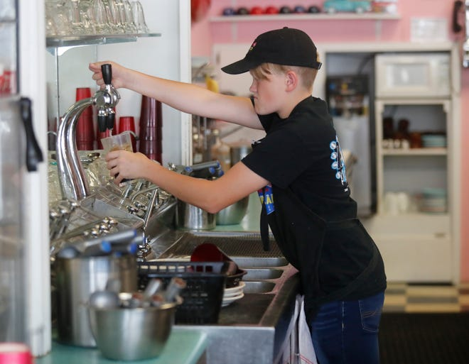 Ryan Gage makes a cherry coke at the soda fountain at the Holly Hop Ice Cream Shoppe Monday, July 12, 2021.
