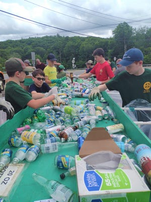 STERLING - Members of Sterling Boy Scouts troops 1 and 189 sort some of the record number of recyclable and redeemable cans and bottles collected June 26 in the parking lot of the Sterling Municipal Light Department.
