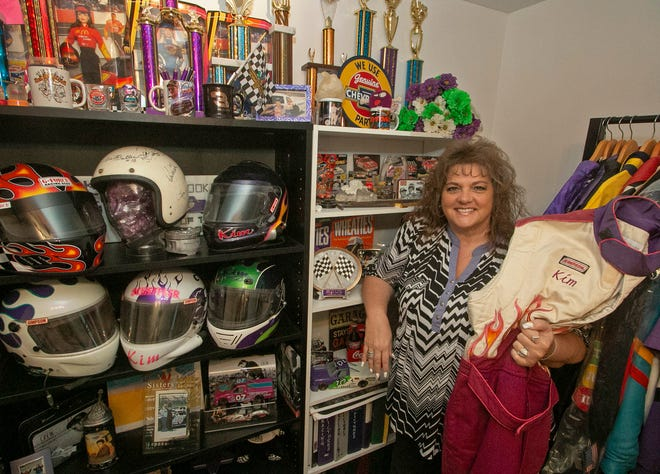 Kim Scheffler stands next to her wall of trophies and memories that she racked up through her years of short track racing.