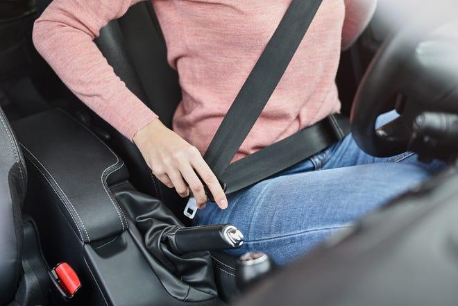 Woman fastening seat belt in car.