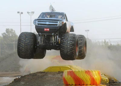 The monster truck Excaliber goes airborne as it races around an obstacle course during the Monster Truck Show at the 2010 Monroe County Fair. The fair is seeking volunteers to assist visitors in finding seats at grandstand shows planned during the Aug. 1-7 fair.