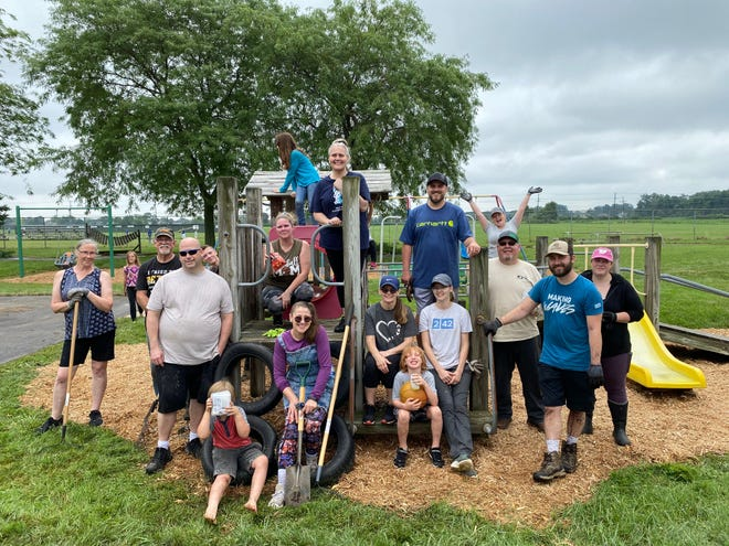 Volunteers pose at a play structure after work was completed Saturday at the Monroe County Intermediate School District.