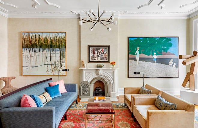 For this circa 1900 West Village townhome in New York, interior designer Kathleen Walsh designed the living room around a vibrant area rug. The bluish-green upholstered sofa and apricot-taupe chairs draw from secondary colors in the rug. The wall art also relates to the blues and tans in the rug.