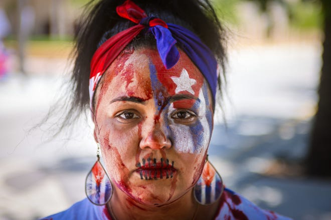 Liannys Sanchez prepares to take part in a rally at West Palm Beach city hall to support anti-government protesters in Cuba, Sunday, July 18, 2021.