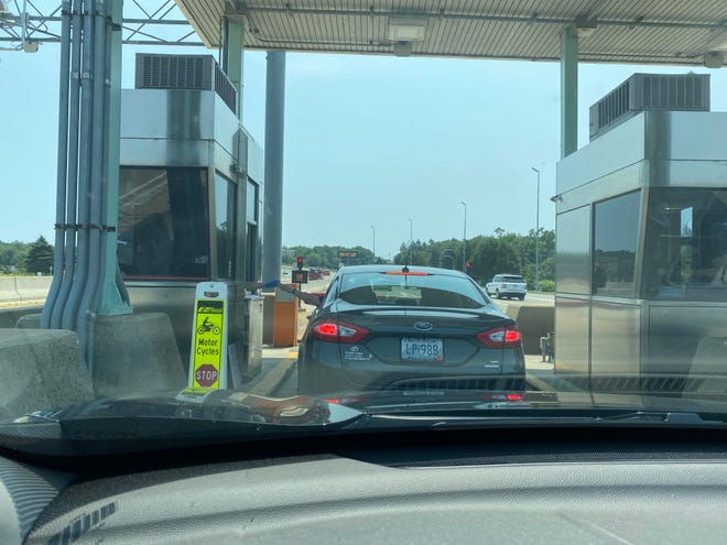 A driver pays the $4 toll to cross the Pell Bridge in July. The toll booths will soon be a thing of the past.