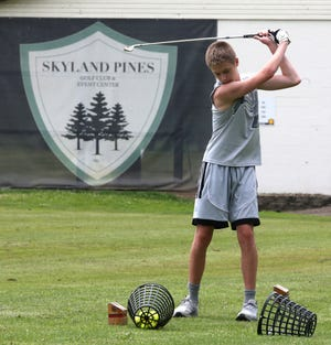 Caleb Smith practices on the driving range Monday at Skyland Pines Golf Club in Canton. The facility will be closing down after Labor Day to make room for an undisclosed business development.