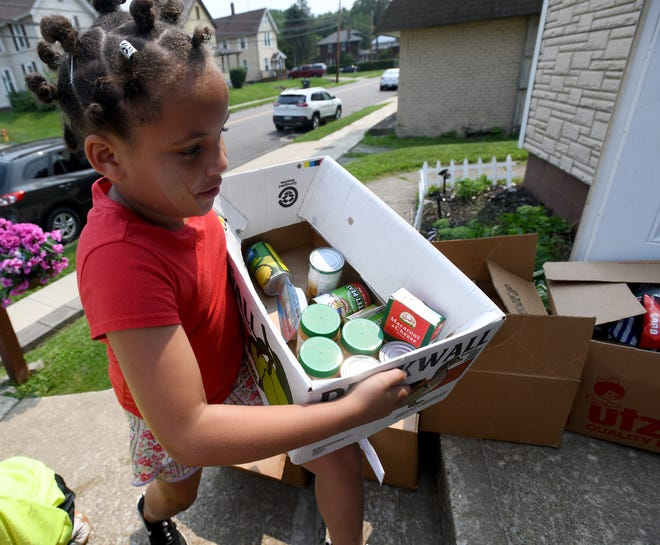 Volunteer Maryilnn Lippert, 8, carries a box of food as New Life Church of God in Christ in Massillon passes out brown bag lunches and food.