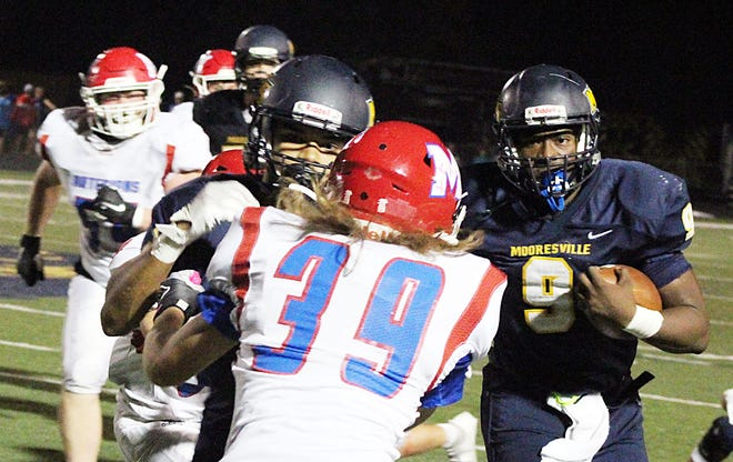 Martinsville cornerback Charles Proctor fights off a Mooresville blocker as he awaits the arrival of Pioneer quarterback Nick Patterson during the teams' Mid-State Conference game last season.