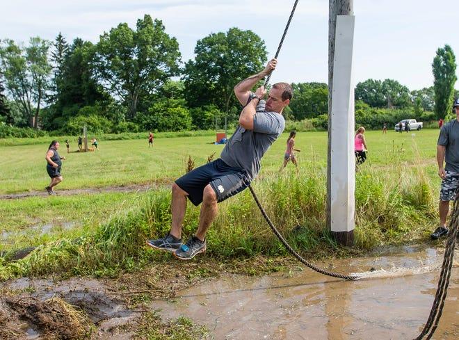 Regan Jones swings over a pool of muddy water at the Marine Mud Run in 2019 at Marian High School in Mishawka. The run returns this Saturday.