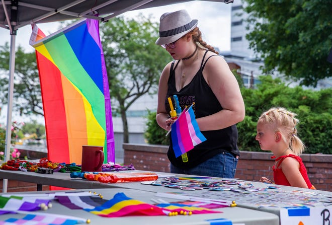 Sisters Ashlynn Yandl, left, and Caterina Yandl look over items at a table during Pride in the Plaza on Sunday at the Jon R. Hunt Plaza in South Bend.