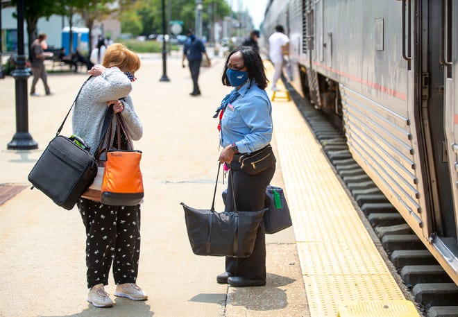 Amtrak train attendant Kenyatta Hardeman helps a passenger with her bags as the Lincoln Service train stops at the Amtrak Station in Springfield, Ill., Monday, July 19, 2021. The Lincoln Service, Carl Sandburg/Illinois Zephyr and Illini/Saluki state-supported Amtrak trains all resumed full-service Monday after reductions of one-half related to the COVID-19 pandemic. [Justin L. Fowler/The State Journal-Register]