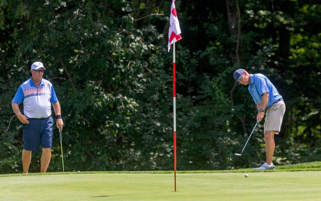 Dave Marshall, on right, follows through on a putt  on the 3rd green as he competes against Bill Hermanson, left,  during the final round of the Norwich Invitational golf tournament, on Sunday at the Norwich Golf Club.