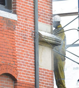 Ben Randall of CD Masonry Restoration in Oxford power washes mortar off brinks  at Killingly Town Hall Monday before the bricks will be repointed later. [John Shishmanian/ NorwichBulletin.com]