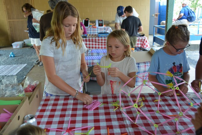 Avery and Kinley Appleby (from left) and Peyton Gibson learn one of the many building stations during the STEM Rocks program at the Somerset Union Street Playground Monday.