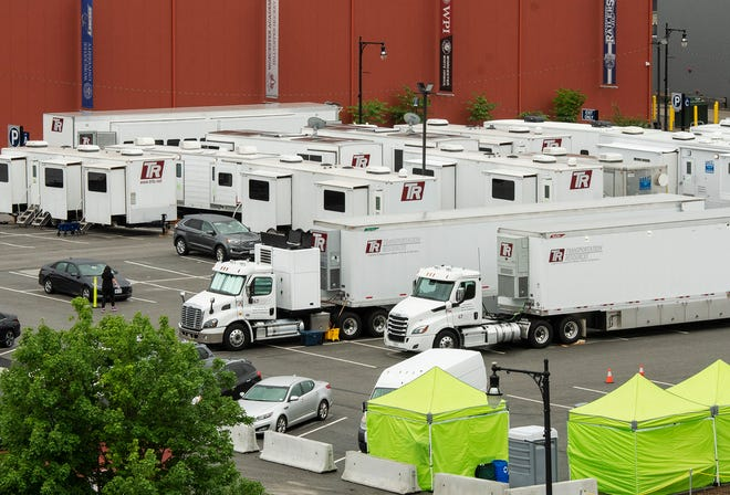 Movie production trucks and trailers fill a parking lot on Temple Street Monday.