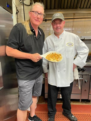Nick Kessler showing off the Lobster Mac and Cheese with Chef David Brown at the Mill Wharf Restaurant.