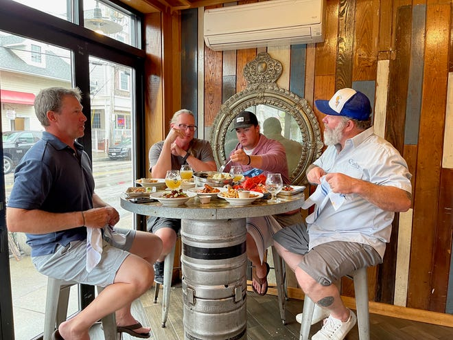 """A feast of feasts! Nick Kessler with Capt. Mike Evensen and Capt. Conor Doherty of """"Go Get 'Em Sport Fishing,"""" and Chef Brian Houlihan of The Galley Kitchen and Bar get ready to chow down on their catch of the day."""