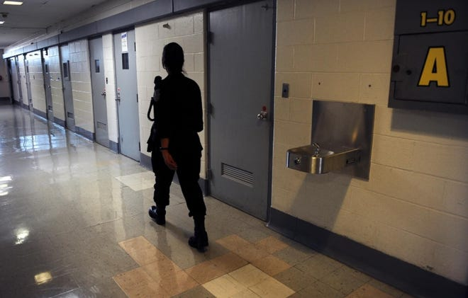 A corrections officer does rounds in a cell block at MCI-Framingham in this 2012 file photo.
