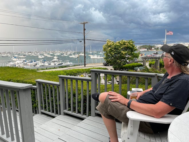 """Nick enjoys the view of Scituate Harbor from the deck of The Inn at Scituate Harbor during a break in filming a segment of """"Road Trip Masters."""""""
