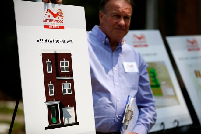 Real estate agent Don Johnson displays a rendering of a new home slated to be built during a ground breaking ceremony in East Price Hill's Incline District in Cincinnati on Monday, July 19, 2021. A series of new, modern homes with two-car garages, multiple bathrooms and bedrooms are slated to be built in the west side neighborhood, the group announced.