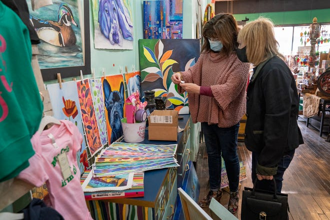 Lillian Li, 62, of Grosse Pointe, left, helps customer Mary Anne Meathe, 79, of Grosse Pointe Woods fill a Mother's Day order at Leaf and Blossom in Detroit on Wednesday, May 5, 2021.  This Detroit based business sells artwork and crafts created by 22 Detroiters. The store opened in December 2020 in response to art shows shutting down due to the pandemic.