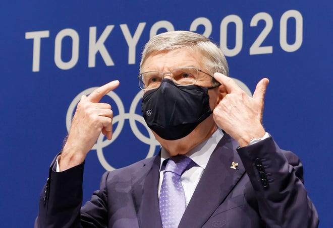 IOC President Thomas Bach gestures during a press conference at the Main Press Center, ahead of the Tokyo 2020 Olympic and Paralympic Games in Tokyo, Saturday, July 17, 2021. The first resident of the Olympic Village has tested positive for COVID-19, Tokyo Olympic organizers said on Saturday.