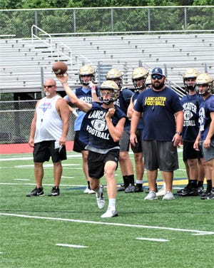 Lancaster junior quarterback Trace VanGundy gets set to throw a pass while head coach Bryan Schoonover looks on during the Golden Gales' 7-on-7 passing scrimmage against Fairfield Union.