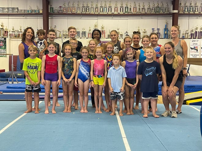 Amanda Wilfong (back left) stands with her team of gymnast at Mid Ohio Gymnastics in Marion, Ohio. Wilfong spends much of her time in the gym as the owner and coach of different teams, all at different age levels.