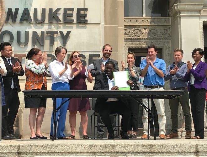 Milwaukee County Executive David Crowley holds up a signed Right to Counsel bill on July 19, 2021.