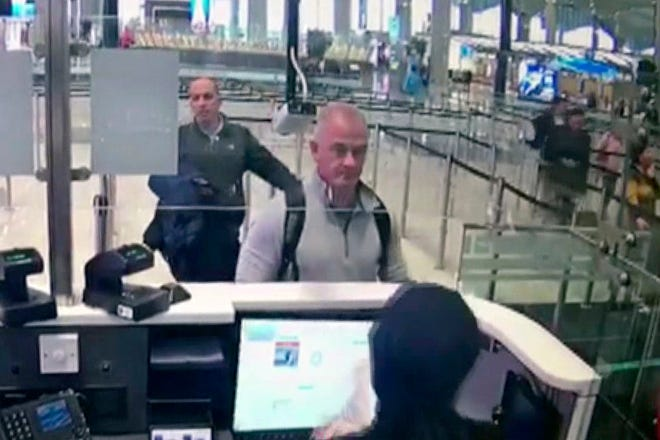This Dec. 30, 2019, image from security camera video shows Michael L. Taylor, center, and George-Antoine Zayek at passport control at Istanbul Airport in Turkey. A Tokyo court handed down prison terms for the American father Michael Taylor and son Peter accused of helping Nissan's former chairman, Carlos Ghosn, escape to Lebanon while awaiting trial in Japan.