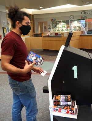 Wyatt Kastl uses a self checkout kiosk on July 19, 2021 at the Westland Public Library.