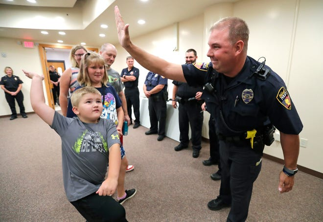Officer Ben Fenhouse high-fives Oliver Stadtmueller, 5, as his parents, Doug and Melissa Stadtmueller, look on with his sister, Chloe, 12, and other police officers Monday at the Oshkosh Police Department. The Stadtmueller family was rescued from a fire at their home Saturday and wanted to meet the officers who saved them.