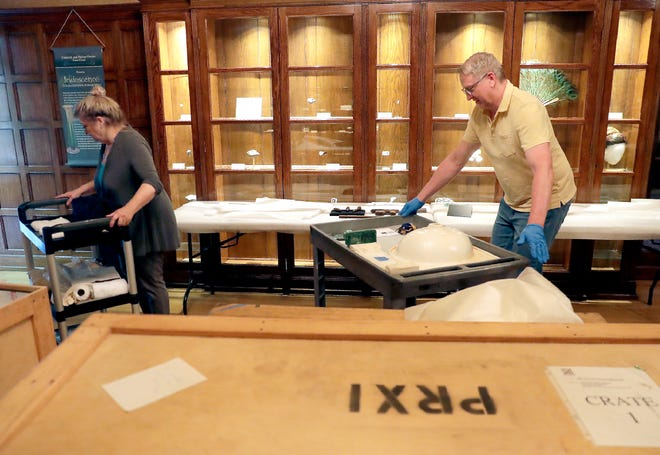 """Debra Daubert, Oshkosh Public Museum Curator of Exhibitions, and Jeff Taylor, Director of Collections with Experimental Media Group, set up displays Thursday of salvaged from the wreck of the White Star liner RMS Titanic at the Oshkosh Public Museum. """"Titanic: The Wisconsin Connection"""" will be on display starting Wednesday through Oct. 13."""