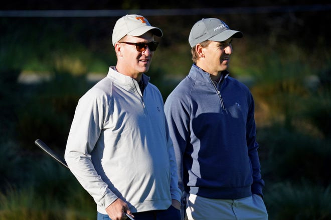In this Feb. 6, 2020 file photo, Peyton Manning, left, and his brother Eli Manning wait to hit from the first tee of the Spyglass Hill Golf Course during the first round of the AT&T Pebble Beach National Pro-Am golf tournament in Pebble Beach, Calif. During a Monday night telecast, Peyton Manning accused the New England Patriots of cheating.