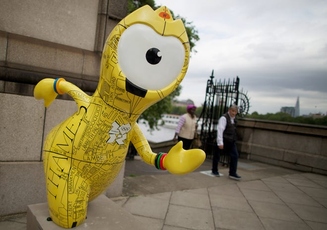 Pedestrians walk past a sculpture of the London 2012 Olympic Games mascot Wenlock decorated with a street map of Westminster as part of the London Prepares programme of cultural events and attractions in London on July 17, 2012.