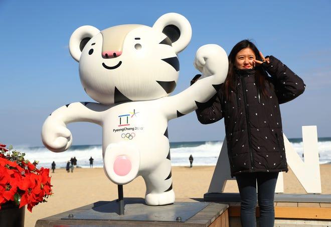 A woman poses with Olympic mascot Soohorang on Anmok Beach at the Sea of Japan at the PyeongChang 2018 Winter Olympic Games.