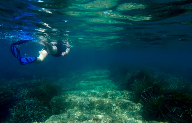 Yiannis Violaris of the Cyprus Antiquities Department snorkels over submerged stone remains of a 2,400 year-old harbor said to be built Alexander the Great's successors near the modern-day resort town of Limassol, Cyprus.