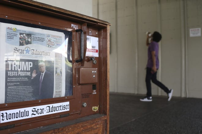 A man walks past a newspaper stand at the international airport in Honolulu on Oct. 2. [AP PHOTO/CALEB JONES/FILE]