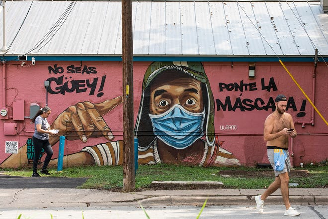 People pass a mural urging people to wear masks painted on Marcelino's restaurant in East Austin on July 20. Health leaders last week said all Travis County residents, including those vaccinated against the coronavirus, should return to wearing masks in public to avoid a surge in coronavirus cases as the delta variant continues to spread.