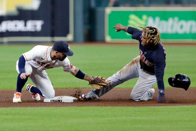 Houston Astros second baseman Jose Altuve, left, attempts the tag as Cleveland's Jose Ramirez, right, is safe on a steal at second during the first inning of a baseball game Monday, July 19, 2021, in Houston. (AP Photo/Michael Wyke)