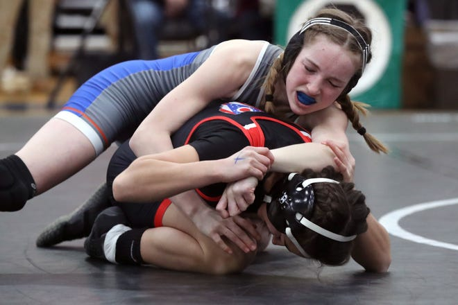 Olentangy Orange's Lucy Scheibeck battles New Richmond's Kaitlyn Fisher at 106 pounds during the girls state wrestling tournament Feb. 20. The Pioneers finished third as a team, behind champion Marysville.
