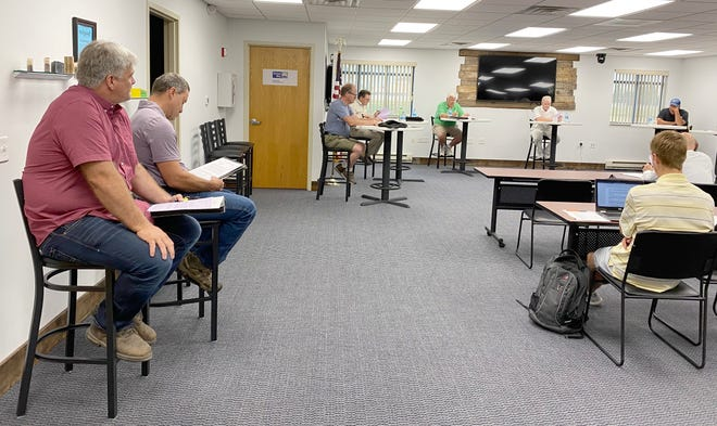 At Tuesday's CHEDA Board meeting at Valley Technology Park, Bryan Boll, left foreground, listens to a question posed by CHEDA Board President Wayne Melbye, in green shirt in the background. Seated next to Boll is Phil Schramm of Boll Family Farms.