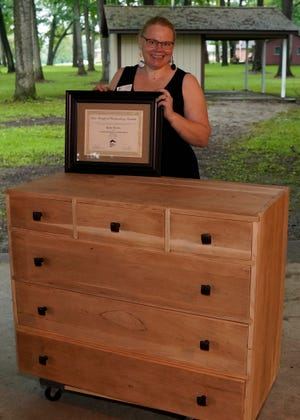 Katie Tilton, a Tecumseh resident, stands with the handmade dresser/sideboard she created while a part of the Sam Beauford Woodworking Institute's yearlong Furniture Making and Wood Design diploma program. Tilton is one of seven inaugural graduates in the woodworking program, who earned their diplomas Friday evening.