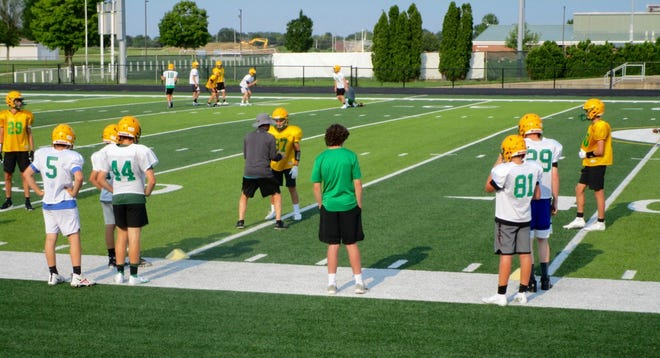 Players look on as coach demonstrates technique to teammate during summer practice