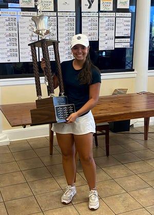 Kate Joyner holds the trophy after winning the Junior Citrus golf tournament.
