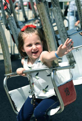 Ava Dowen, 3, of Monroe, waves to her mom while riding the kiddie swing at the 2015 Monroe County Fair. There will be no kiddie rides offered on the first day of the 2021 fair due to COVID-19.