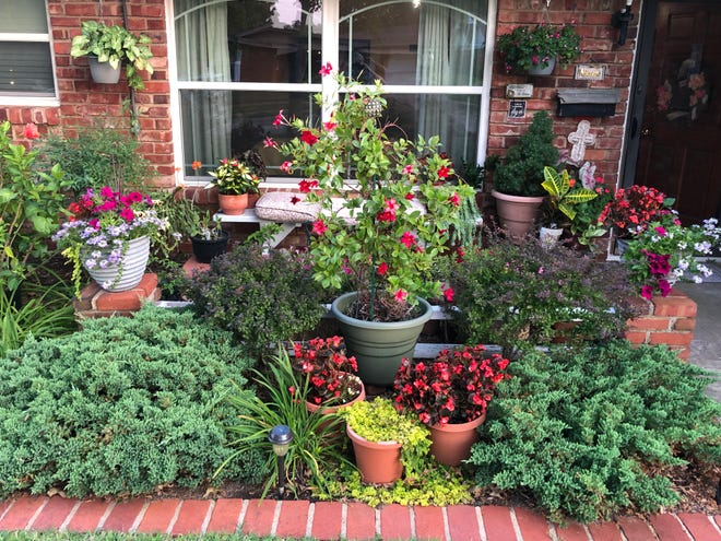 Nice use of decorative container gardens on a front porch and highlighted in a front flower bed.